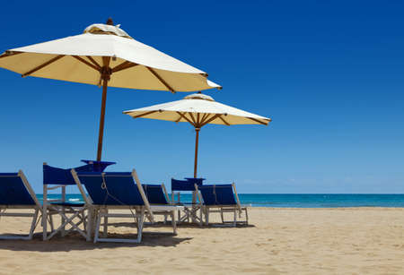 Deck chairs under an umbrella in the sand against the blue sea Stock Photo - 7312387