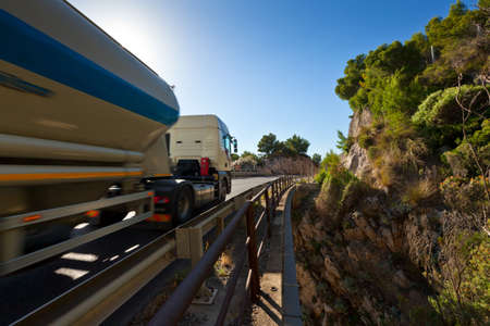 The modern truck driving fast on mountain bridge on a sunny day photo