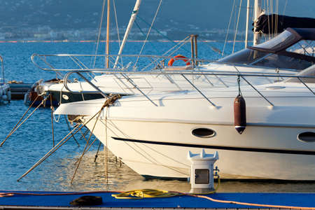 Two white yachts in the sea bay at anchor at the pier, lit the evening sun photo