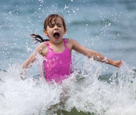 Little Girl lachen und Weinen in der Spray von Wellen auf dem Meer an einem sonnigen Tag Standard-Bild