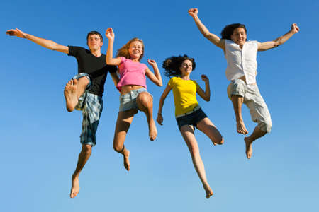 Four young boys and girls jumping on a background of blue sky photo