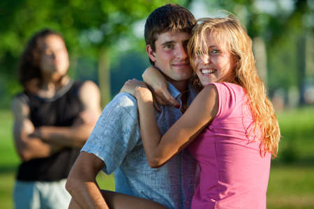 A couple of lovers embrace in a park on the background of the third young man