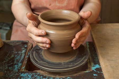 alfarero: Las manos de un alfarero, creando una jarra de barro en el círculo, primeros planos