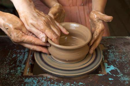 teaches: Potter teaches cooking pots his assistant. Close-up