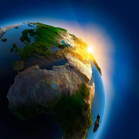 the rising sun: Los rayos del sol desde el sol naciente iluminan la tierra en el espacio ultraterrestre