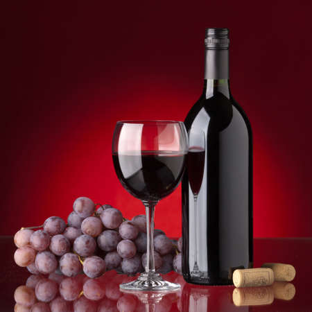 Bottle and glass of red wine, grape and cork on a red background photo