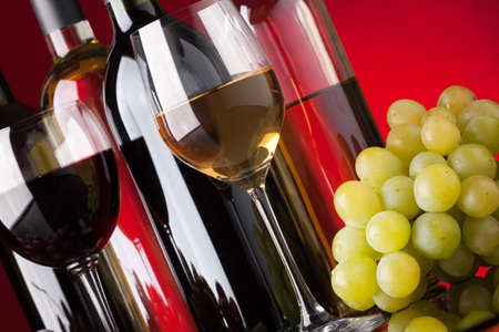 Several bottles of red and white wine glasses and grapes on a red background photo