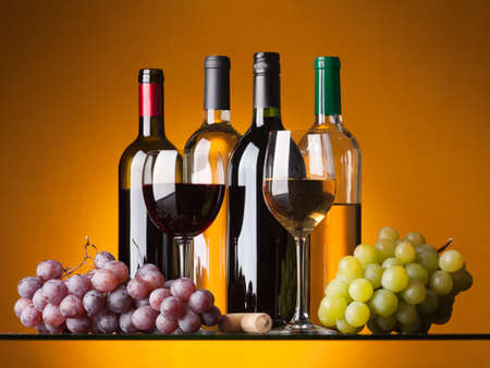 grapes on vine: Several bottles of white and red wine, two glasses and grapes on an orange background Stock Photo