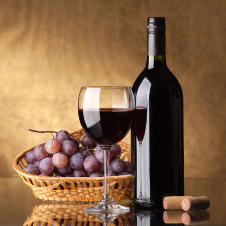 bunch of grapes: A bottle of red wine, glass and grapes on a golden background