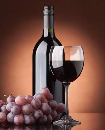A bottle of red wine, glass and grapes on a brown background photo
