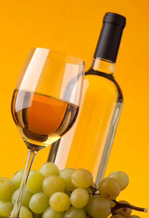 Bottom view of a glass of white wine bottle and grapes on a yellow background photo