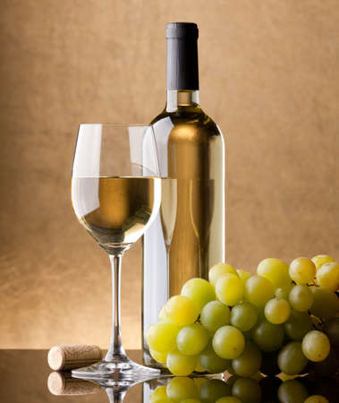 A bottle of white wine, glass and grapes on a golden background photo