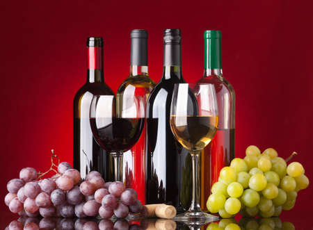 Several bottles of white and red wine, two glasses and grapes on a red background photo