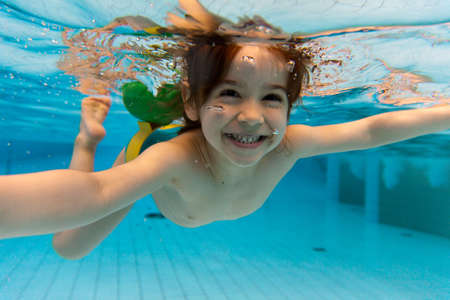 The little girl in the water park swimming underwater and smiling photo
