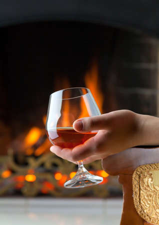 A glass of cognac on the background of a burning fireplace photo