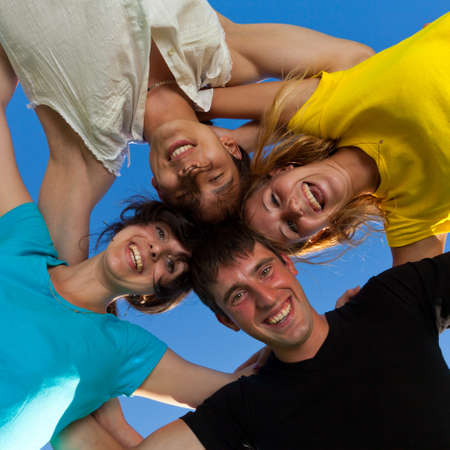 The four friends, embracing, has formed a circle and bent over a photographer photo