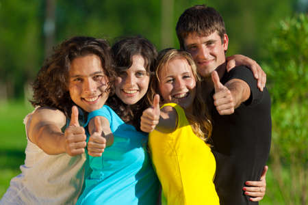 Young group of happy friends showing thumbs up sign together outdoor in the park photo