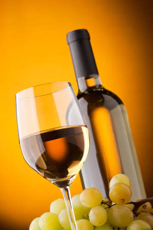 tasteful: Bottom view of a glass of white wine bottle and grapes on a yellow background Stock Photo