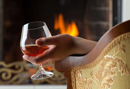 fireside: A glass of cognac on the background of a burning fireplace with a brass openwork lattice