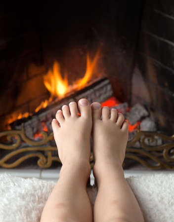 Childrens bare feet are heated in the fire in the fireplace with a brass openwork lattice photo