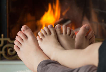 kids feet: Bare legs a little girl and her sisters are heated by an open fire hearth