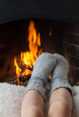 Childrens feet in warm woolen socks heated in the fire in the fireplace