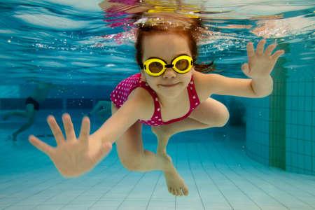girl underwater: Het kleine meisje in het water park zwemmen onder water en glimlachen