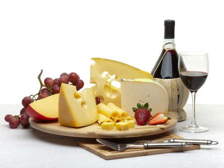 queso: Composici�n de queso, uvas, botellas y vasos de vino y fresas en una bandeja ronda de madera sobre un mantel blanco, aislado en un fondo blanco