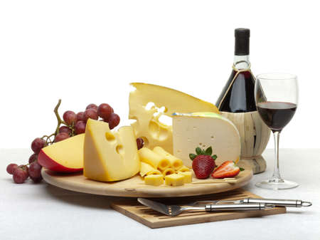 cheese knife: Composition of cheese, grapes, bottles and glasses of wine and strawberries on a wooden round tray on a white tablecloth, isolated on a white background