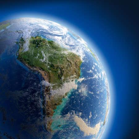 Tierra con el alivio, la superficie detallada, mar transparente y la atmósfera, iluminada por la luz del sol