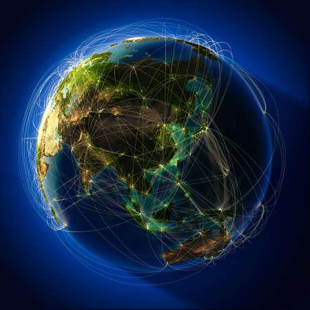 La planète Terre très détaillée dans la nuit, éclairé par derrière le soleil du soir, avec des continents en relief, éclairée par la lumière des villes, translucides et de l'océan de réflexion. Terre est entourée par un réseau lumineux, ce qui représente les grandes voies aériennes basées sur réel