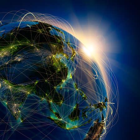 zeměkoule: Vysoce detailní planeta Země v noci, osvětlené vycházejícího slunce, s reliéfní kontinenty, osvětlená světlem měst, průsvitná a reflexní oceánu. Země je obklopena světelným sítí, což představuje hlavní letecké trasy na základě skutečných dat Reklamní fotografie