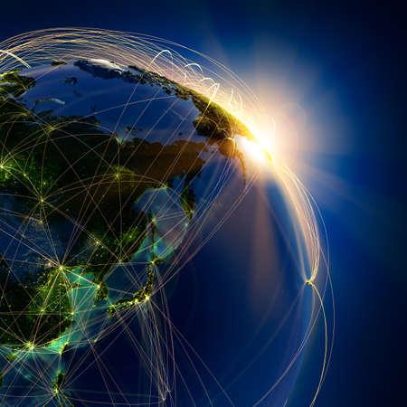 El planeta Tierra altamente detallado en la noche, iluminada por el sol naciente, con los continentes en relieve, iluminados por la luz de las ciudades, translúcidos y de la tierra al mar de reflexión está rodeado por una red luminosa, en representación de las principales rutas aéreas basadas en datos reales Foto de archivo