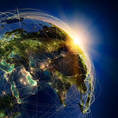 globo terraqueo: El planeta Tierra altamente detallado en la noche, iluminada por el sol naciente, con los continentes en relieve, iluminados por la luz de las ciudades, transl�cidos y de la tierra al mar de reflexi�n est� rodeado por una red luminosa, en representaci�n de las principales rutas a�reas basadas en datos reales Foto de archivo