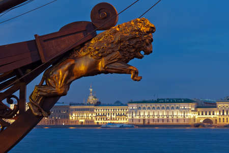 View of the Palace Embankment  In the foreground, a decorative sculpture of a lion on the bow of sailing ship  Twilight, white night  St  Petersburg  Russia photo