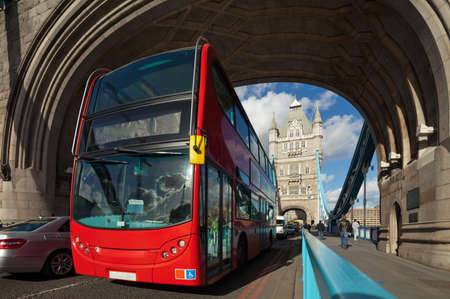 decker: The famous Tower Bridge in London, UK. Double-decker bus passes under the arch of the tower. Sunny day. Photograph taken with the tilt-shift lens, vertical lines of architecture preserved Stock Photo