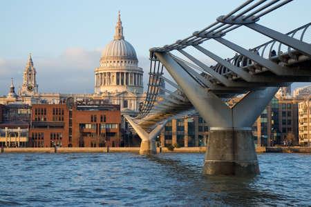 Der iconic Ansicht von London - die berühmte Fußgängerzone Millennium Bridge über die Themse mit Blick auf St. Pauls Cathedral in den warmen Strahlen der untergehenden Sonne