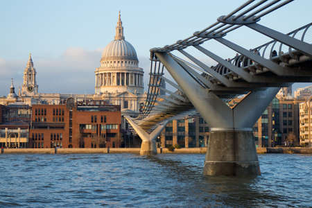 The iconic view of London - the famous pedestrian Millennium Bridge over the Thames with views of St. Pauls Cathedral in the warm rays of the setting sun Stock Photo