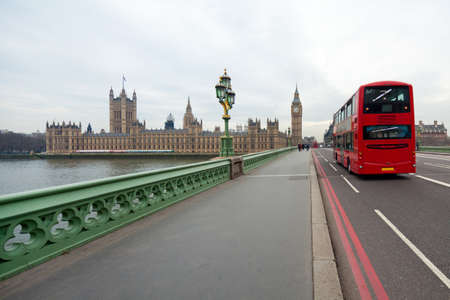 Westminster Bridge with views of the British Parliament and Big Ben. London red double decker bus passes nearby