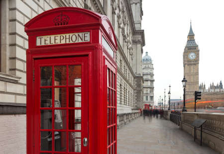 Traditional red telephone box in London public phone - a symbol of the city. Fragment of booths with the Big Ben in the background of the evening