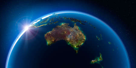 Planet Earth at night with the rising sun with the light of cities illuminating a detailed exaggerated relief. Australia and New Zealand. 3D rendering.