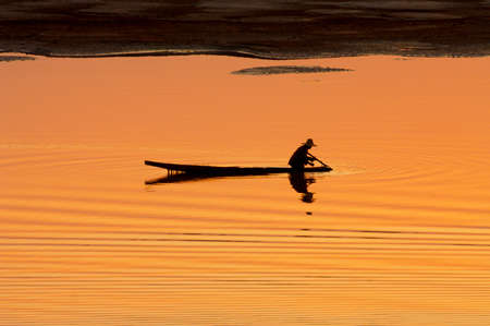 vientiane: Silhouette of boatman at sunset on the Mekong river in Vientiane, Laos. Stock Photo
