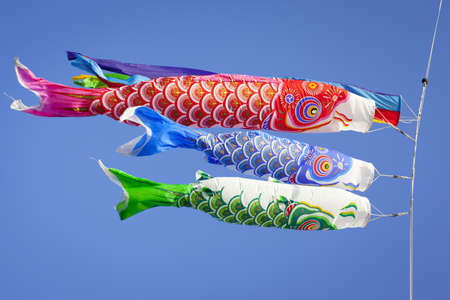 Colourful carp streamers or Koinobori flutter in the wind. The carp shaped wind socks are flown to celebrate Childrens Day, a national holiday in Japan. Stock Photo
