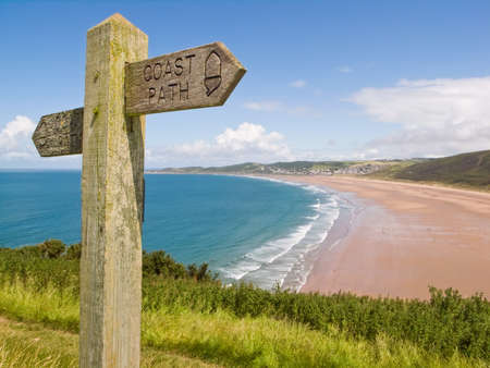 devon: Coastal path with a sign, alongside Woolacombe beach in Devon, England.