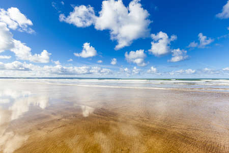 Empty beach with fluffy clouds reflected in the wet sand, Saunton Sands in North Devon, UK  photo