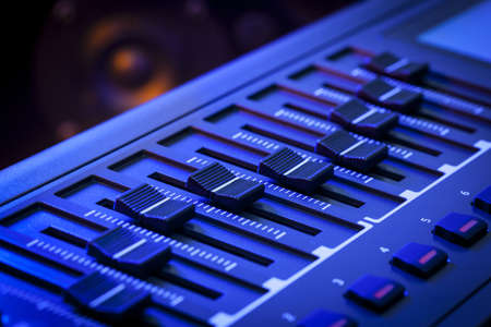 fader: Close-up of a row of faders on a MIDI controller Keyboard with a speaker out of focus in the background
