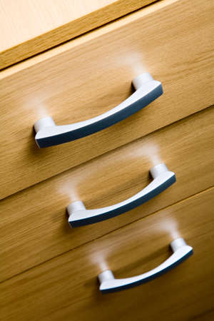 filing cabinet: close up on the three drawers of a wooden filing cabinet in an office
