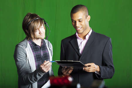 Floor manager runs through scripts with a Television Presenter in a green screen studio