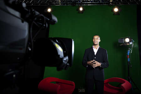 Television presenter in a green screen studio with television camera out of focus in the foreground