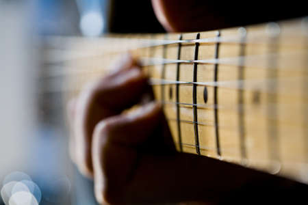 Close-up of the fretboard of an electric guitar with a hand out-of-focus in the background Stock Photo - 17937537